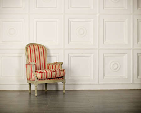 red chair: One classic armchair against a white wall and floor. Copy space