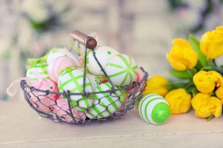 flores color pastel: Flores en colores pastel, los huevos de Pascua coloridos en la cesta Foto de archivo