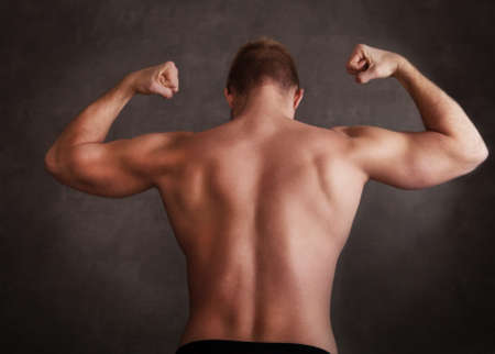 Handsome muscular male model near the wall with copy space photo