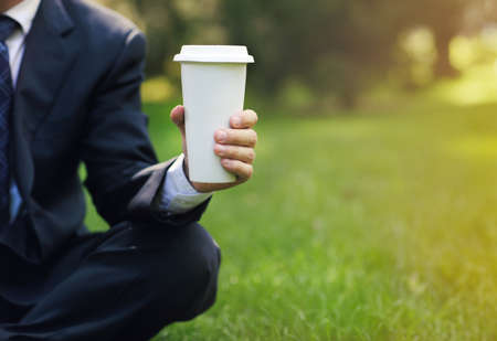 Business man relaxing in a park drinking black coffee in the lotus position. Close up photo