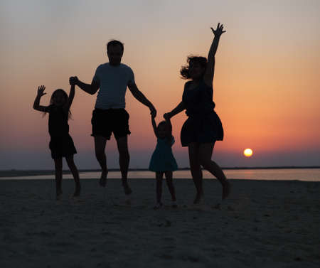 Happy beautiful family jumping on the beach at the sunset time photo