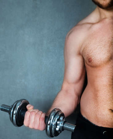 Handsome muscular male model doing exercise for biceps with dumbbells photo
