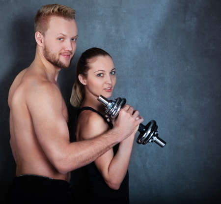 Athletic man and woman with a dumbells near the wall photo