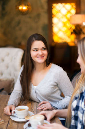 Young women drinking coffee in a cafe. Shallow depth of field photo