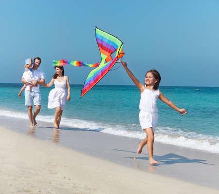 papalote: Familia joven feliz con volar una cometa en la playa