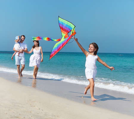 kite flying: Happy young family with flying a kite on the beach