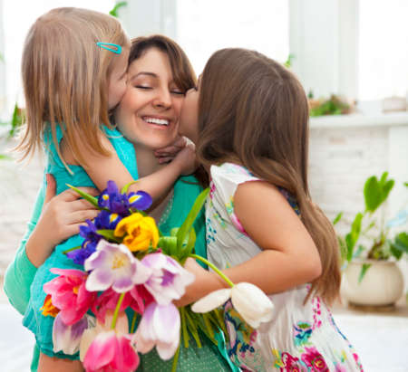 Happy woman and her little daughters in the living room. Mother day concept photo