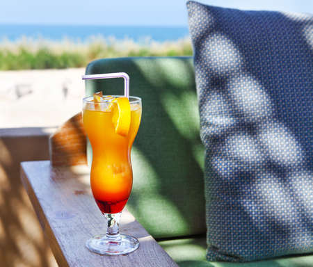 Refreshing orange cocktail on beach table photo