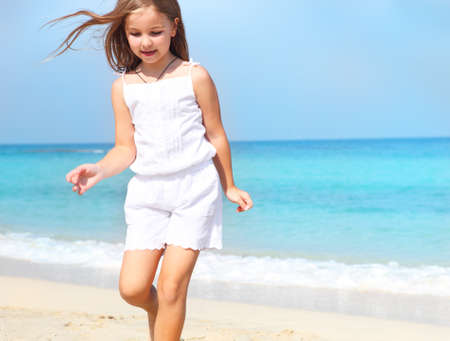Cute little child girl running on the beach photo