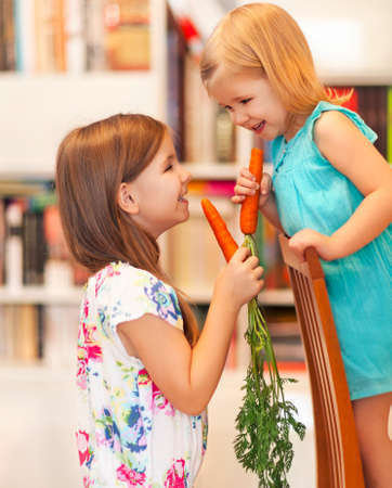 Little smiling girls with organic carrots photo