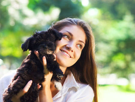 Young brunette woman hugging her lap black dog puppy photo