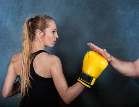 determined: Seriosly female boxer practicing in the boxing ring Stock Photo