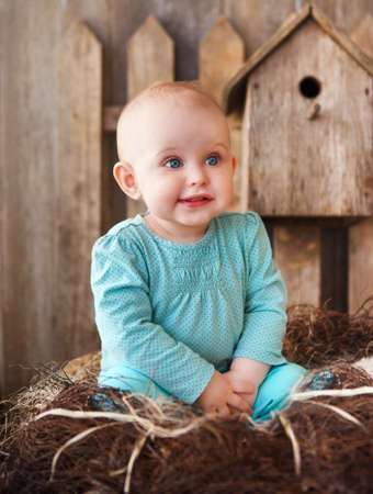 Cute smiling ten month old baby on the wooden background Stock Photo - 27715881