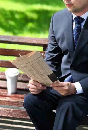 Close up of the hands of the businessman with a newspaper. Outdoors photo