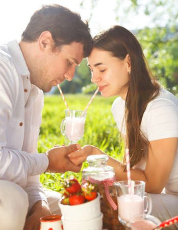 Young happy couple in love drinking milk shake at spring picnic in spring day. Outdoors portrait Stock Photo - 27785372