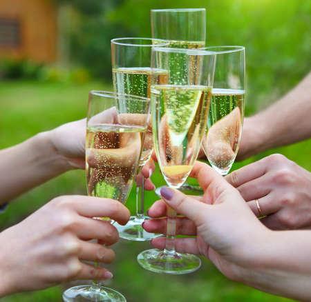 brindisi spumante: Celebration. Persone in possesso di bicchieri di champagne per un brindisi all'aperto
