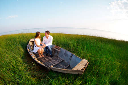 Young happy couple in love in a boat. Outdoors portrait photo