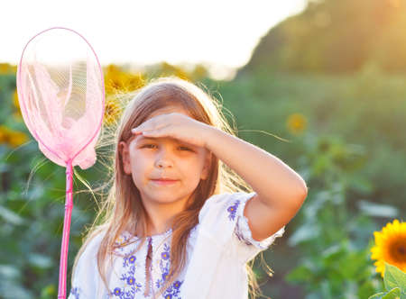 Cheerful little girl playing in a field with insect net in summer evening photo