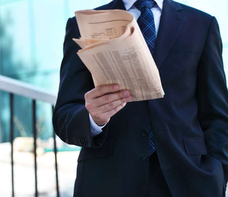 Close up of the hands of the businessman with a newspaper on the stairs. Outdoors photo