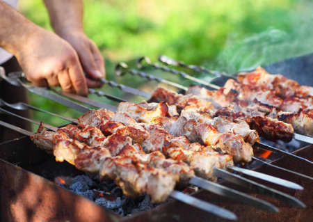 Man cooking marinated shashlik, lamb meat grilling on metal skewer, close up photo