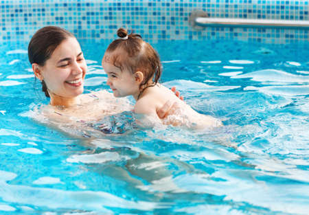 One year baby girl at her first swimming lesson with mother in the pool Stock Photo - 27869969