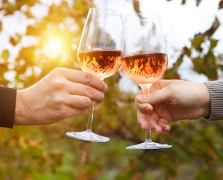 bebiendo vino: Feliz pareja joven disfrutando de unas copas de vino rosado en un viñedo