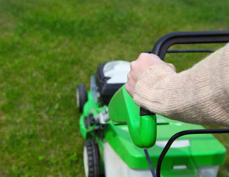 mowing grass: Male gardener mowing the lawn. Gathering Stock Photo