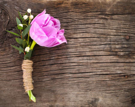 Purple tulip buttonhole for groom on the wooden background. Close up photo