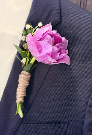 buttonhole: Groom wearing a purple tulip buttonhole. Close up. Toned photo Stock Photo