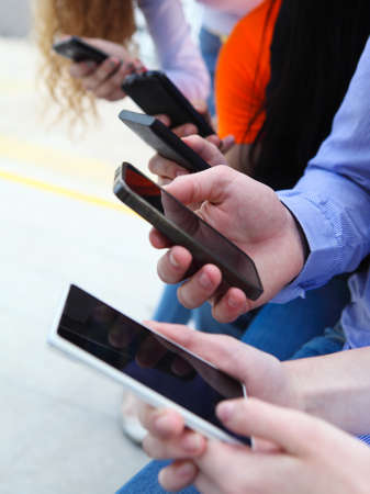 Group of a students chatting with their smartphones at the park. Close up photo