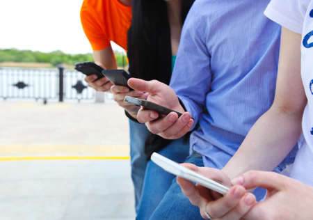 Group of a students chatting with their smartphones at the park. Close up
