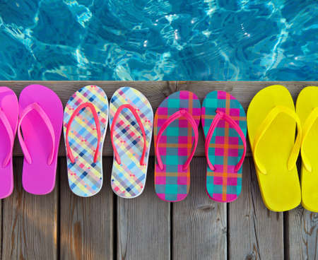 Brightly colored flip-flops on wooden background near the pool photo