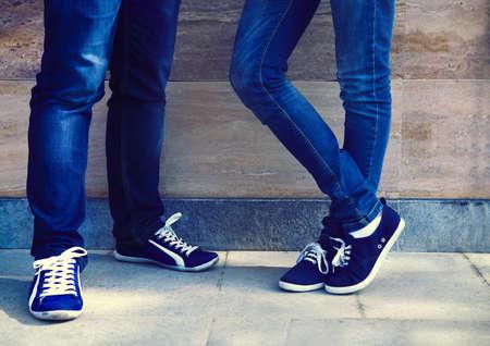 skinny jeans: Un par de vendimia buscando, zapatos deportivos y los pantalones vaqueros flacos de la pareja cerca de la pared. Close up Foto de archivo
