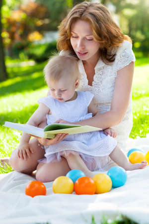 Beautiful Mother And Baby reading outdoors. Happy mum and her Child playing in Park together. Outdoor Portrait of happy family photo