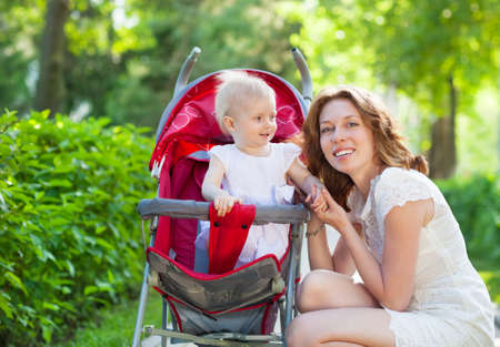 Beautiful young woman with her child in a baby carriage in the park photo