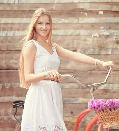 Beautiful blond woman wearing a nice dress having fun in park with bicycle carrying a beautiful basket full of peony flowers. Vintage scenery. Pretty blonde girl with retro look, bike and basket with flowers photo
