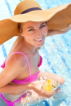Pretty blond woman in a hat enjoying cocktail in a swimming pool photo