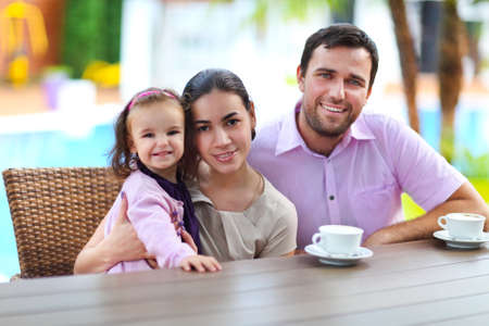 Family with baby girl in the cafe outdoors Stock Photo - 29018911