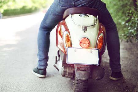scooter: Hombre que monta la vespa vieja retro en una calle de la ciudad. Close up