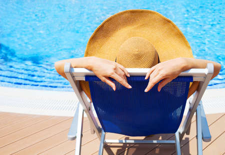 lying forward: Beautiful young woman wearing hat lying on deckchair by swimming pool Stock Photo