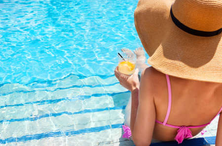 Mujer bastante rubia en un sombrero disfrutar de cócteles en la piscina