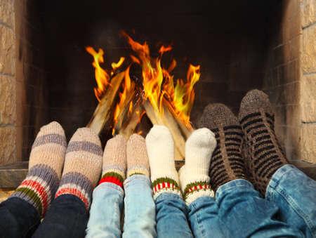 Fötter i en familj bär yllestrumpor uppvärmningen nära eldstaden