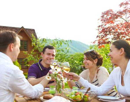 Groep gelukkige vrienden roosteren wijnglazen in de tuin onder het genot van lunch