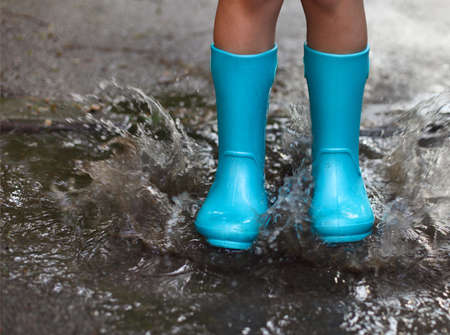 Child wearing blue rain boots jumping into a puddle. Close up