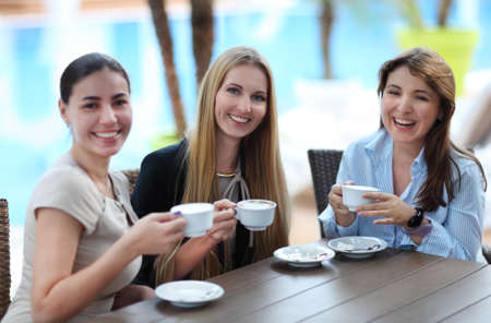 Young women drinking coffee in a cafe outdoors. Shallow depth of field photo