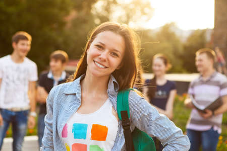 student: Female smiling student outdoors in the evening with friends