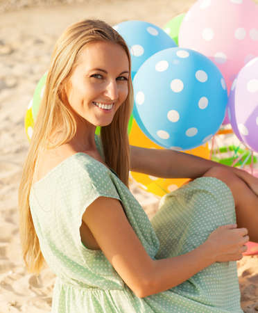 Happy woman on the beach holding colored polka dots balloons photo
