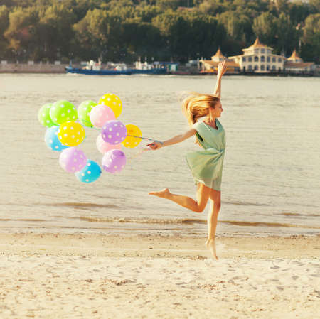 Happy woman jumping on the beach with colored polka dots balloons photo