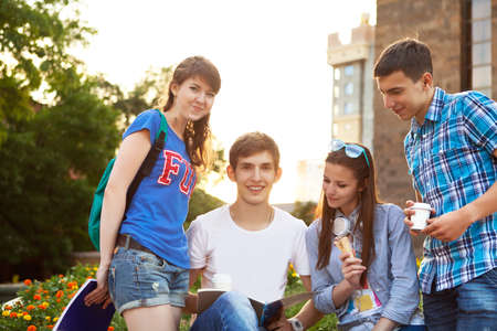 evening class: Group of students or teenagers with notebooks outdoors in summer evening