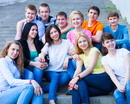 freshmen: Group of smiling teenagers sitting outdoors. Friendship concept
